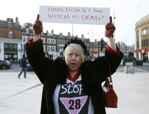 a-reveller-holds-a-sign-to-celebrate-the-death-of-britains-former-prime-minister-margaret-thatcher-at-a-party-in-brixton-south-london-april-8-2013